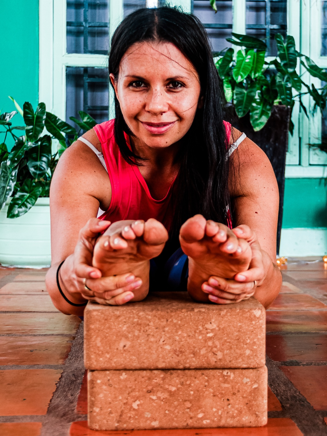 Image of woman with legs outstretched in front of her leaning over and grasping her feet