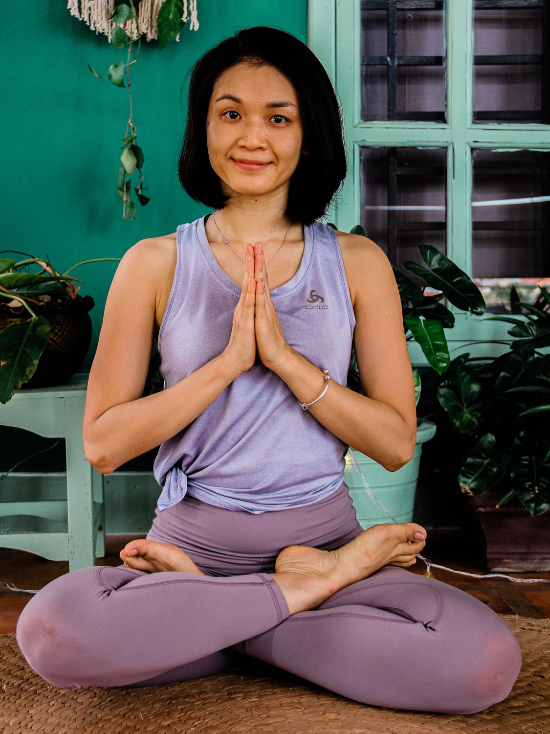 Image of woman wearing purple singlet and purple yoga pants with her hands in prayer position and her legs crossed